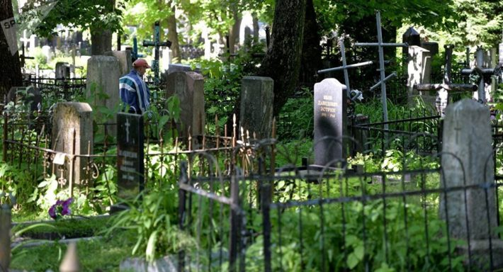 Человек стоит на кладбище