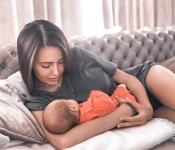 Женщина кормит грудью младенца