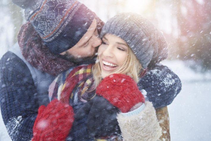 Парень обнимает девушку при снегопаде