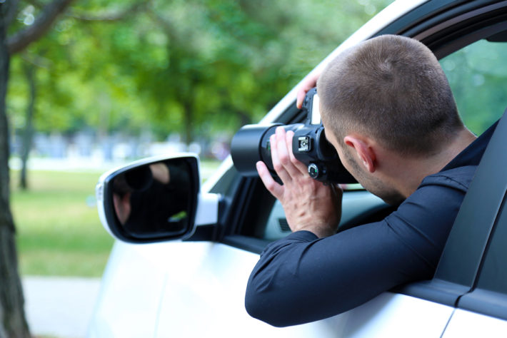 Мужчина с фотоаппаратом сидит в машине