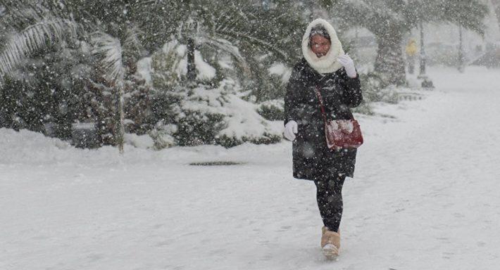 Девушка идет под снегом