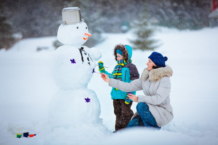 Женщина с ребенком лепят снеговика