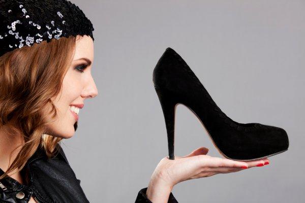 Девушка держит черную туфлю на ладони