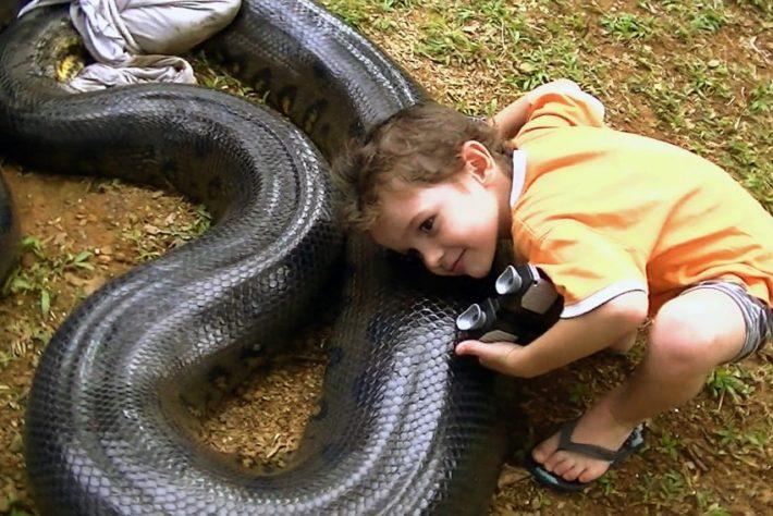Ребенок с огромной черной змеей