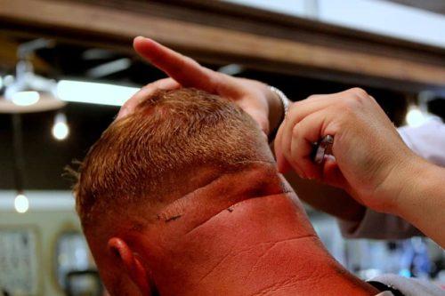 парикмахер бреет клиента