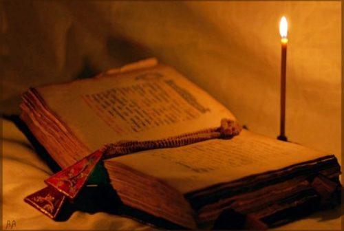 Старинная книга и горящая свеча над ней
