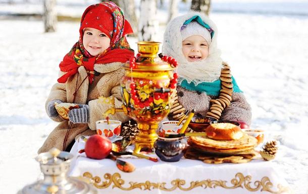 Ряженые маленькие девочки сидят возле самовара