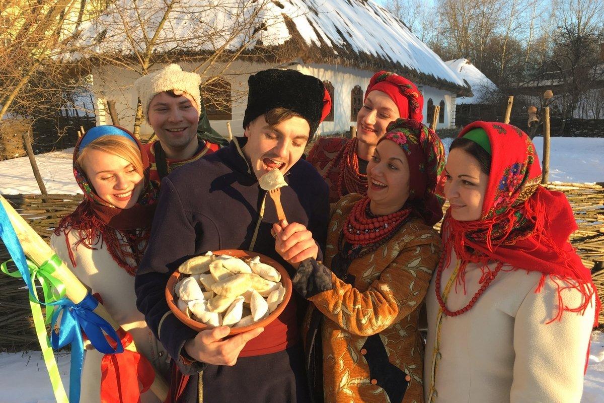 Ряженая молодежь ест вареники на Масленицу