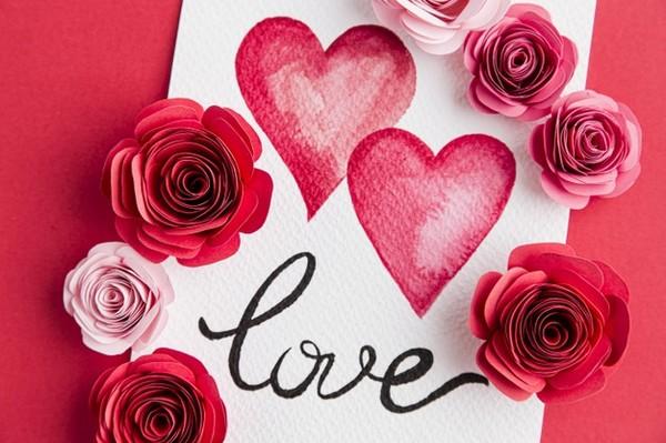 Надпись love, нарисованные сердечки и бумажные розы