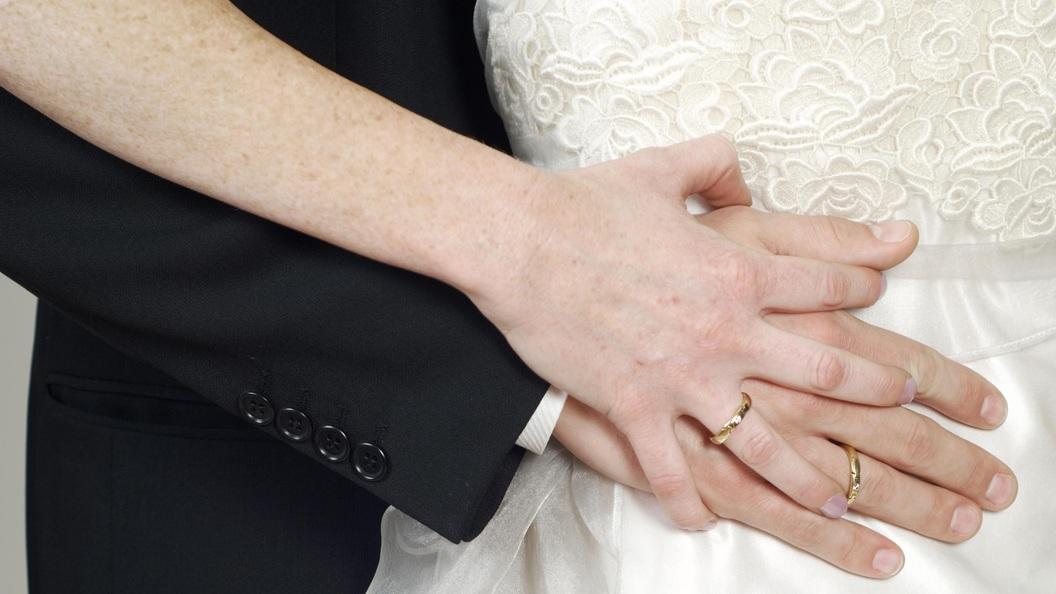 Руки молодоженов с обручальными кольцами