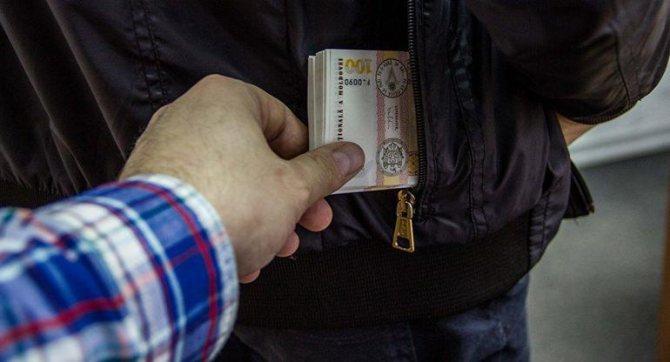Вор вытаскивает пачку денег из кармана