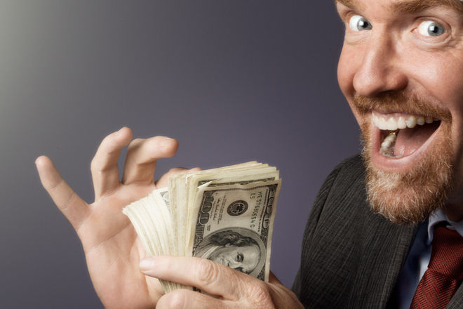 Мужчина радостно пересчитывает деньги