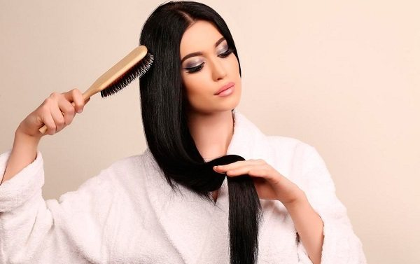Молодая красивая женщина расчесывает свои длинные ухоженные волосы