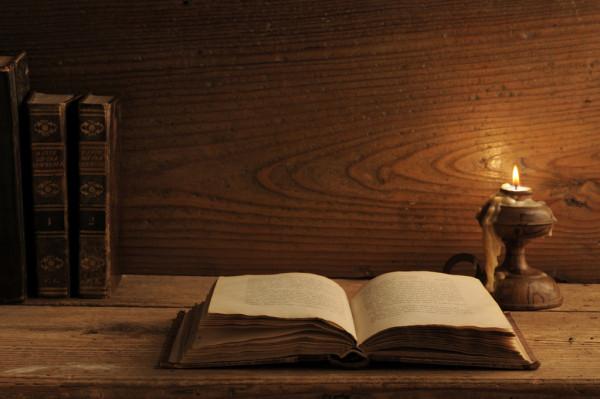 Старинная книга на столе и горящая возле нее свеча