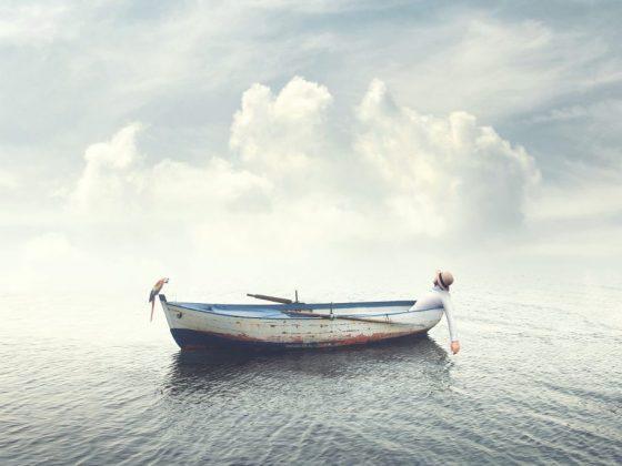 Человек на лодке в ясную погоду и штиль
