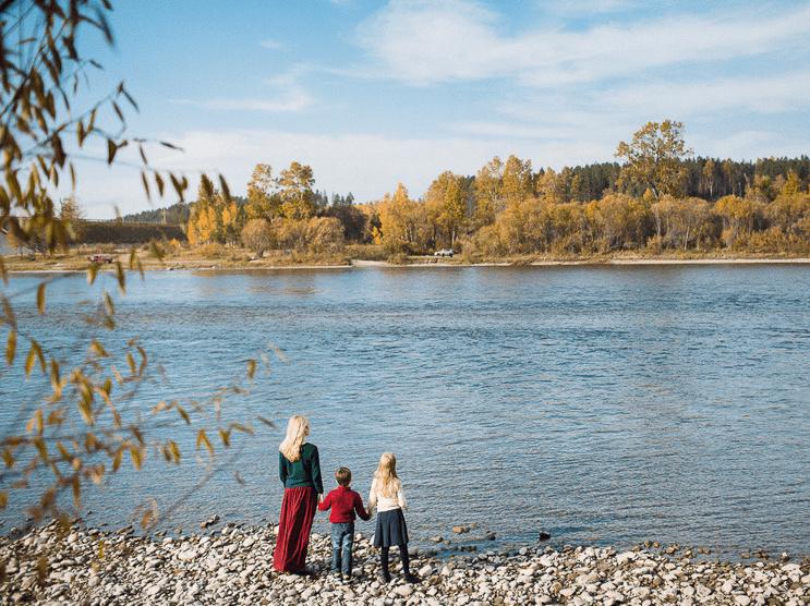Женщина с двумя детьми на каменистом берегу реки