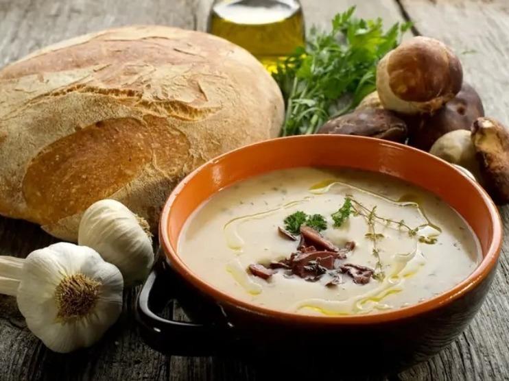 Плошка с грибным супом, хлеб, чеснок и зелень