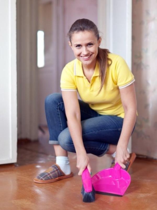 Улыбающаяся девушка собирает мусор с пола, используя щетку и совок