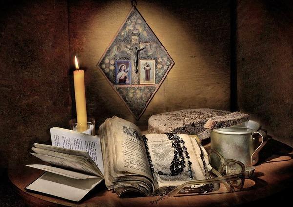 Библия, четки очки, кружка, горящая свеча и святое распятие