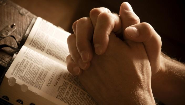 Сложенные руки над молитвословом