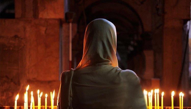 Женщина в платке перед церковным алтарем
