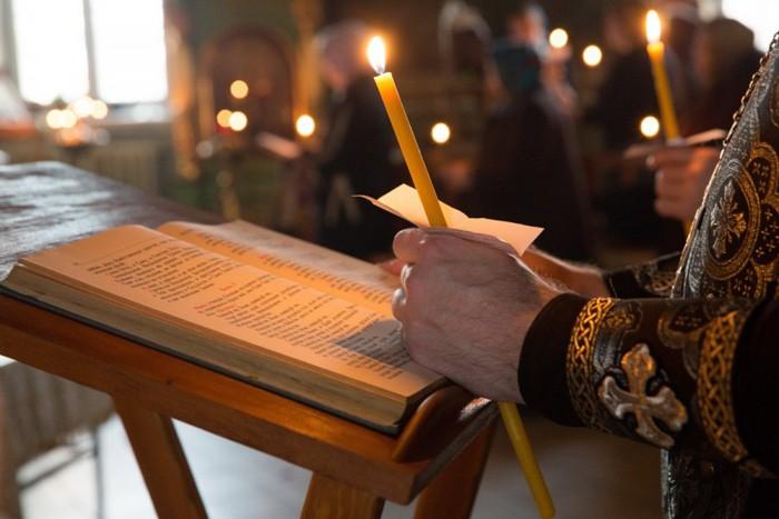 Руки с горящей свечой над молитвословом