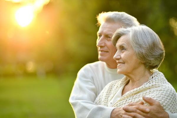 Пожилая пара смотрит в одном направлении и улыбается