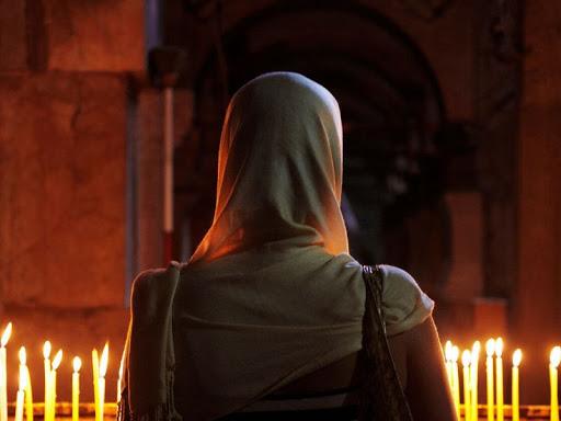 Женская фигура стоит лицом к молитвенному алтарю