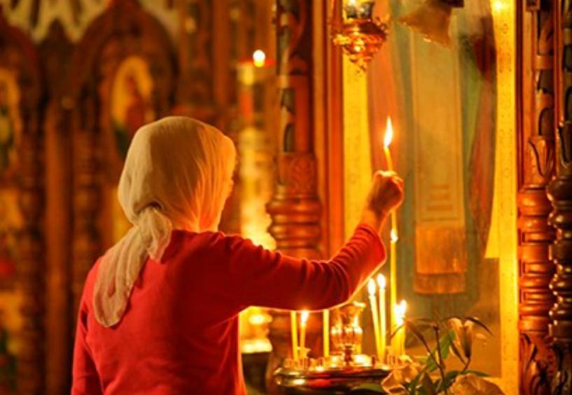 Женщина ставит свечу на алтарь перед образами в церкви