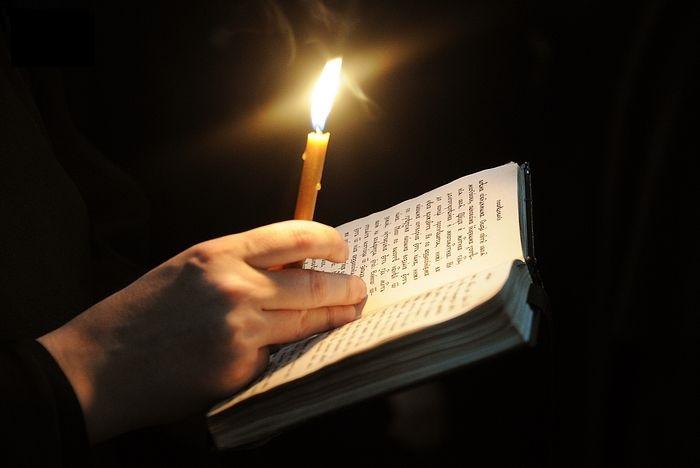 Молитвослов с горящей свечой в руках