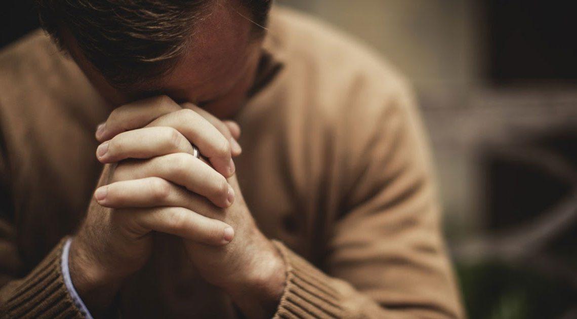 Мужчина склонил голову на руки в молитве