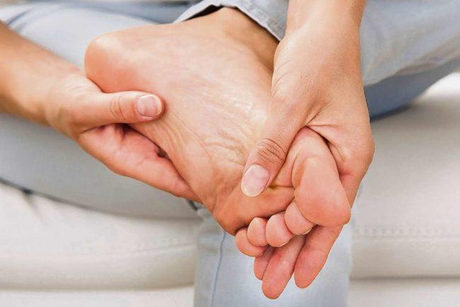 Женская левая ступня, обхваченная руками хозяйки