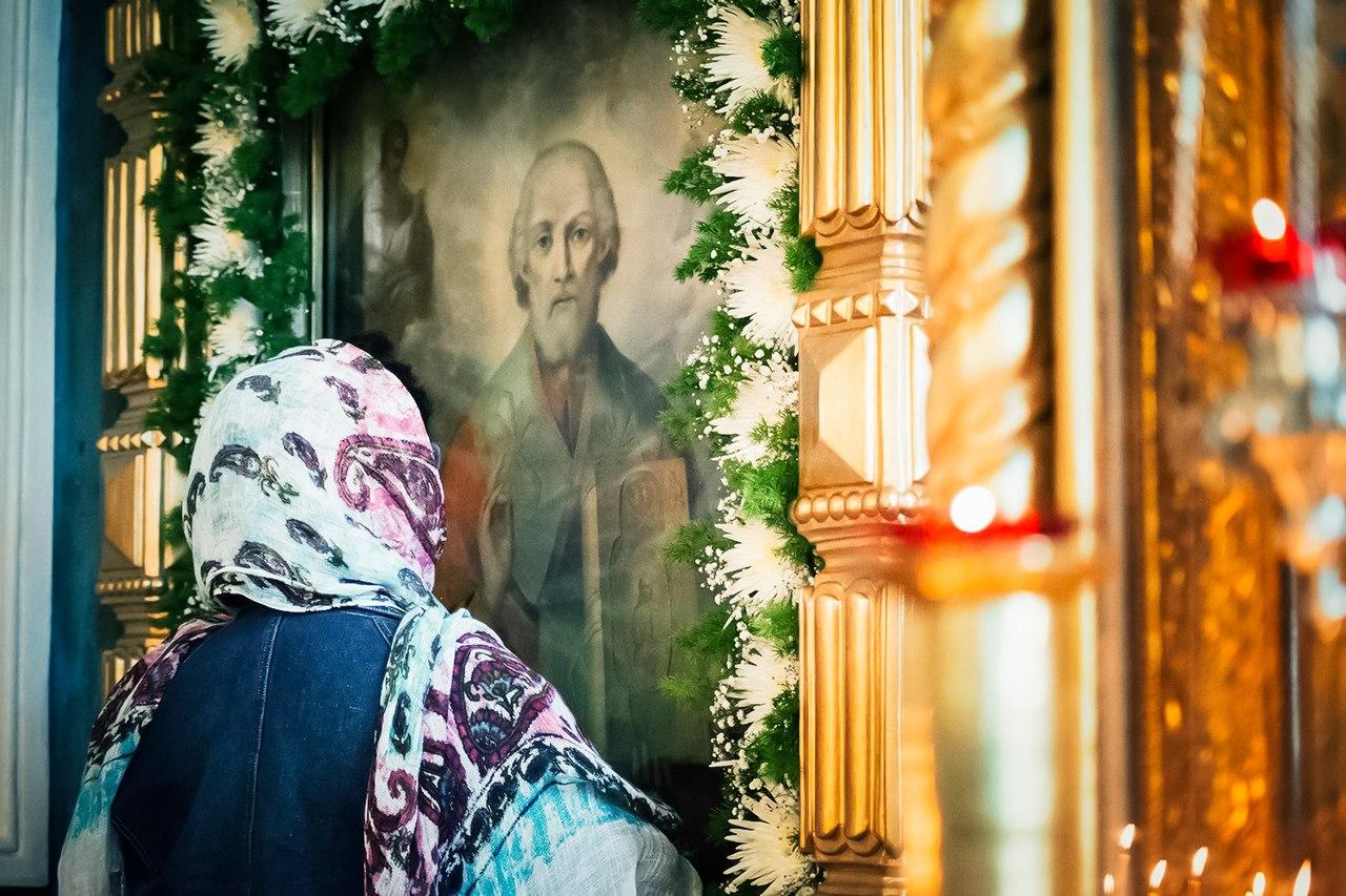 Женщина в платке молится в церкви у иконы Николая Чудотворца