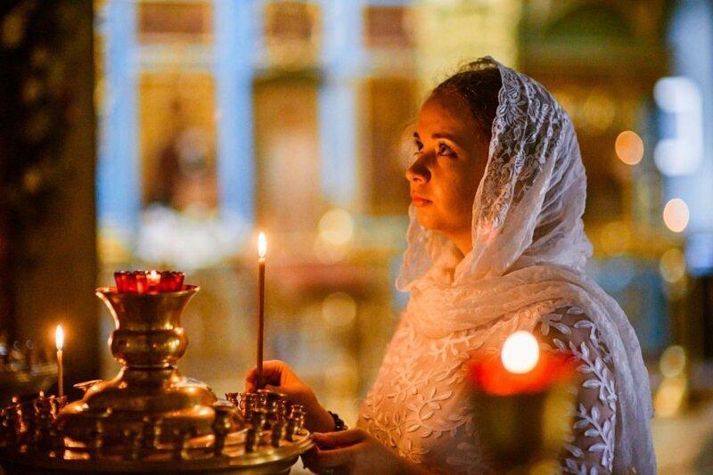 Молодая женщина ставит свечу в церкви