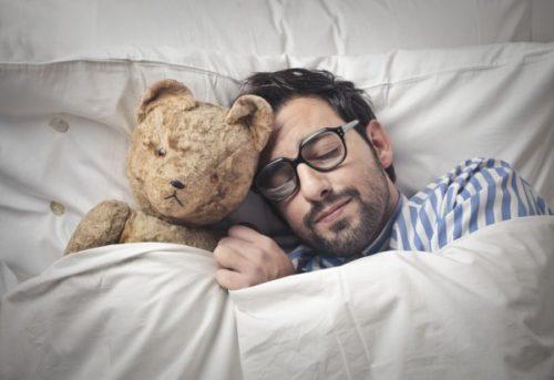 Мужчина спит в постели с плюшевым мишкой