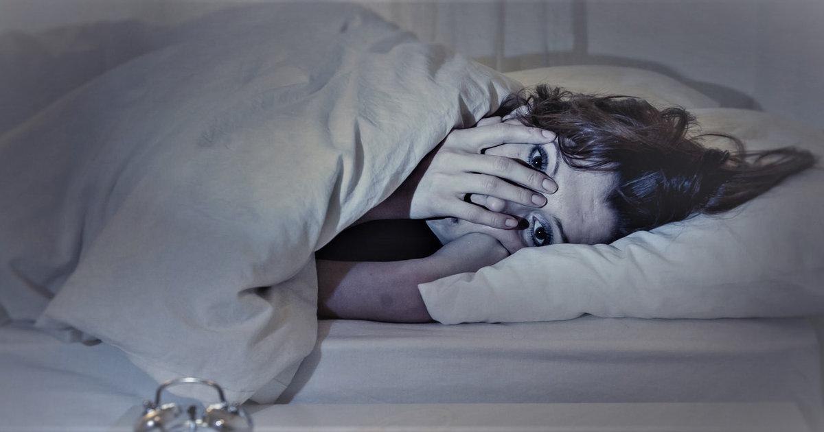 Испуганная девушка в постели во сне