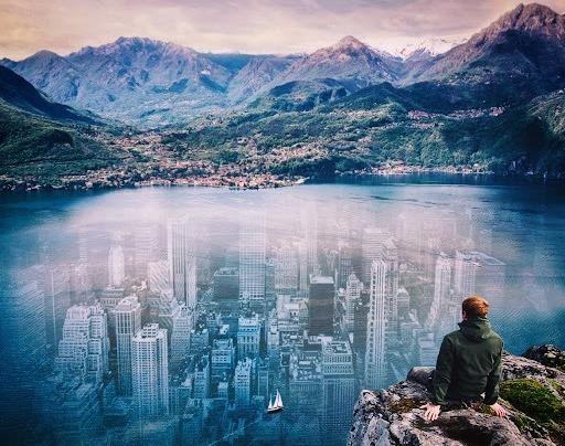 Человек сидит на обрыве над затопленным городом